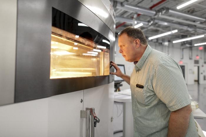 Eric Kouba, superviseur des opérations de fabrication additive, supervise la production sur l'une des 23 imprimantes 3D de l'Advanced Manufacturing Center